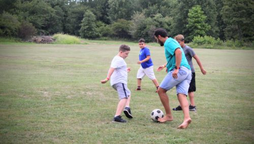 Campers and counselor playing soccer
