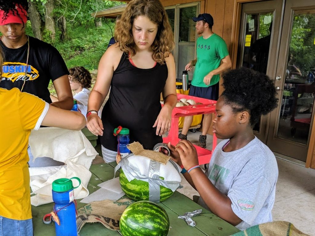 Campers building a shell for their watermelon. Volunteer counselor, David, remembers this as one of his favorite activities.