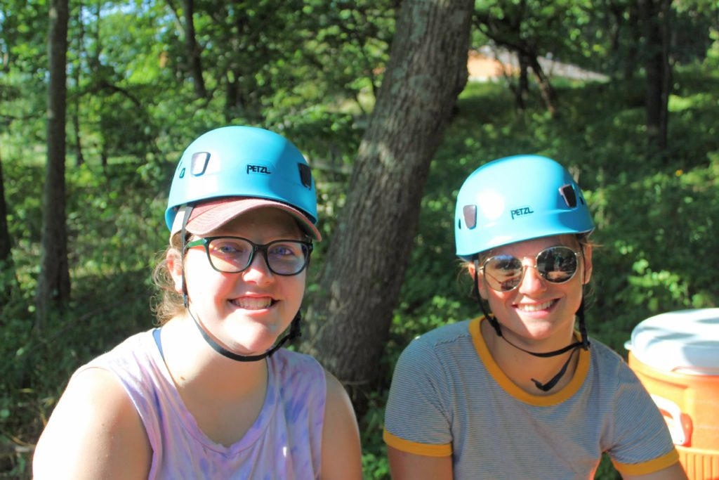 two camp counselors training on high ropes